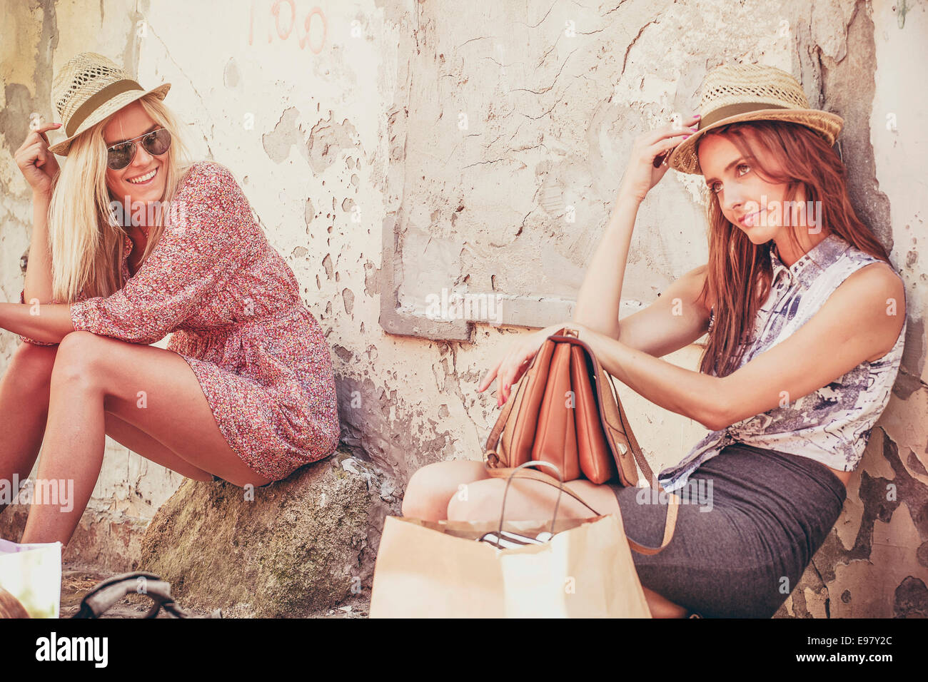 Two women with luggage waiting outdoors looking bored - Stock Image