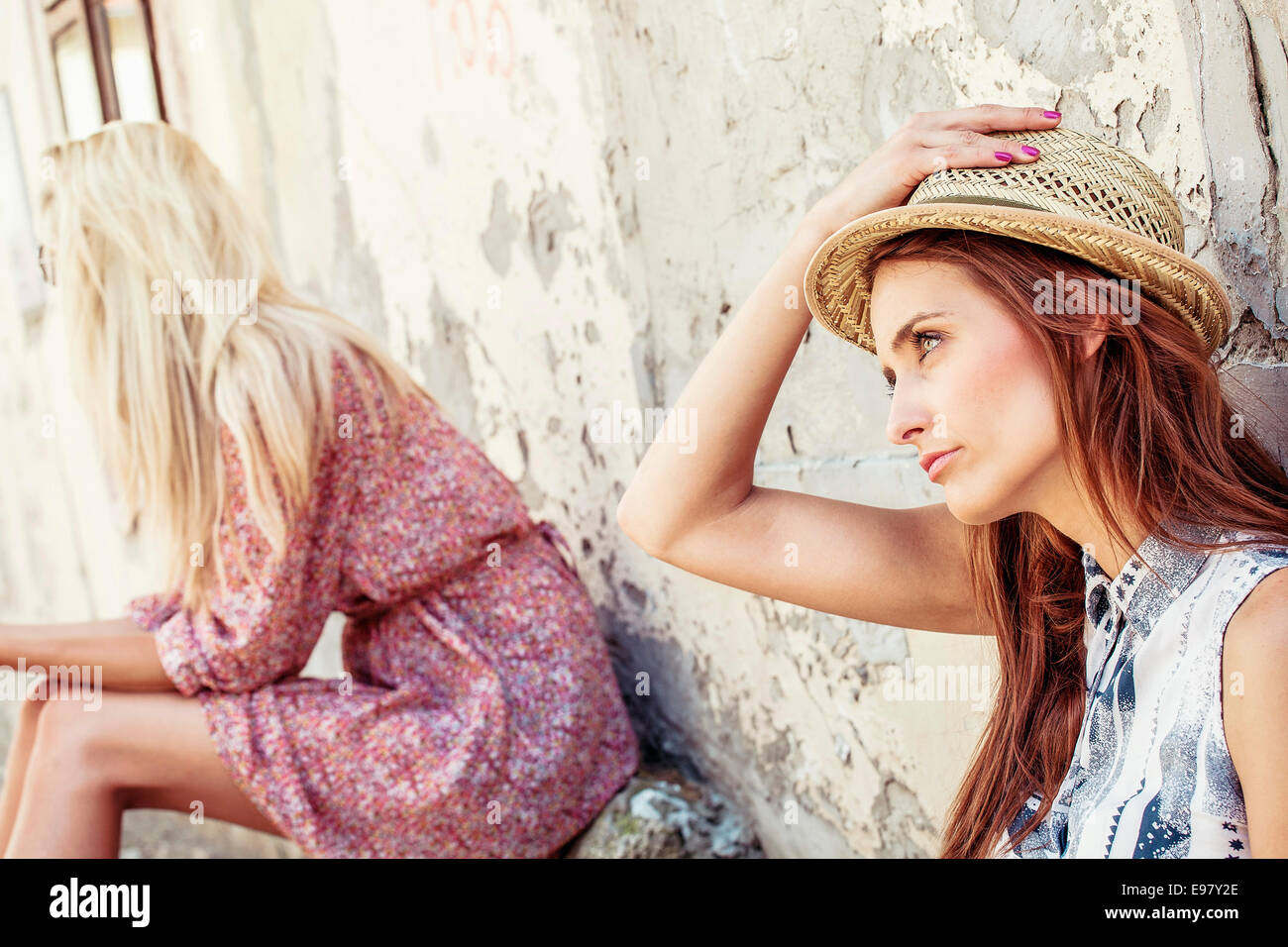 Two bored women with luggage waiting outdoors - Stock Image