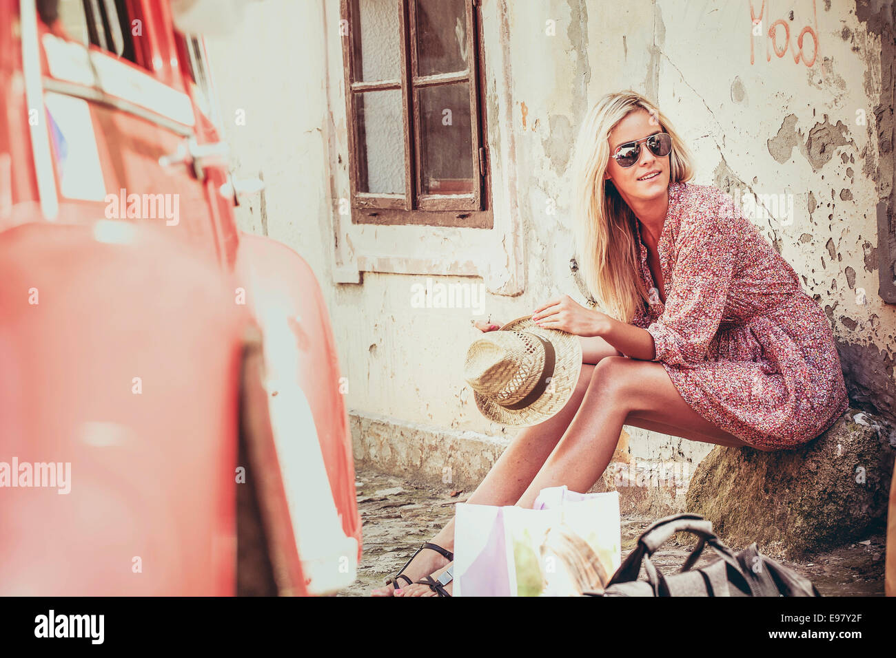 Young woman with blond hair waiting by car outdoors - Stock Image
