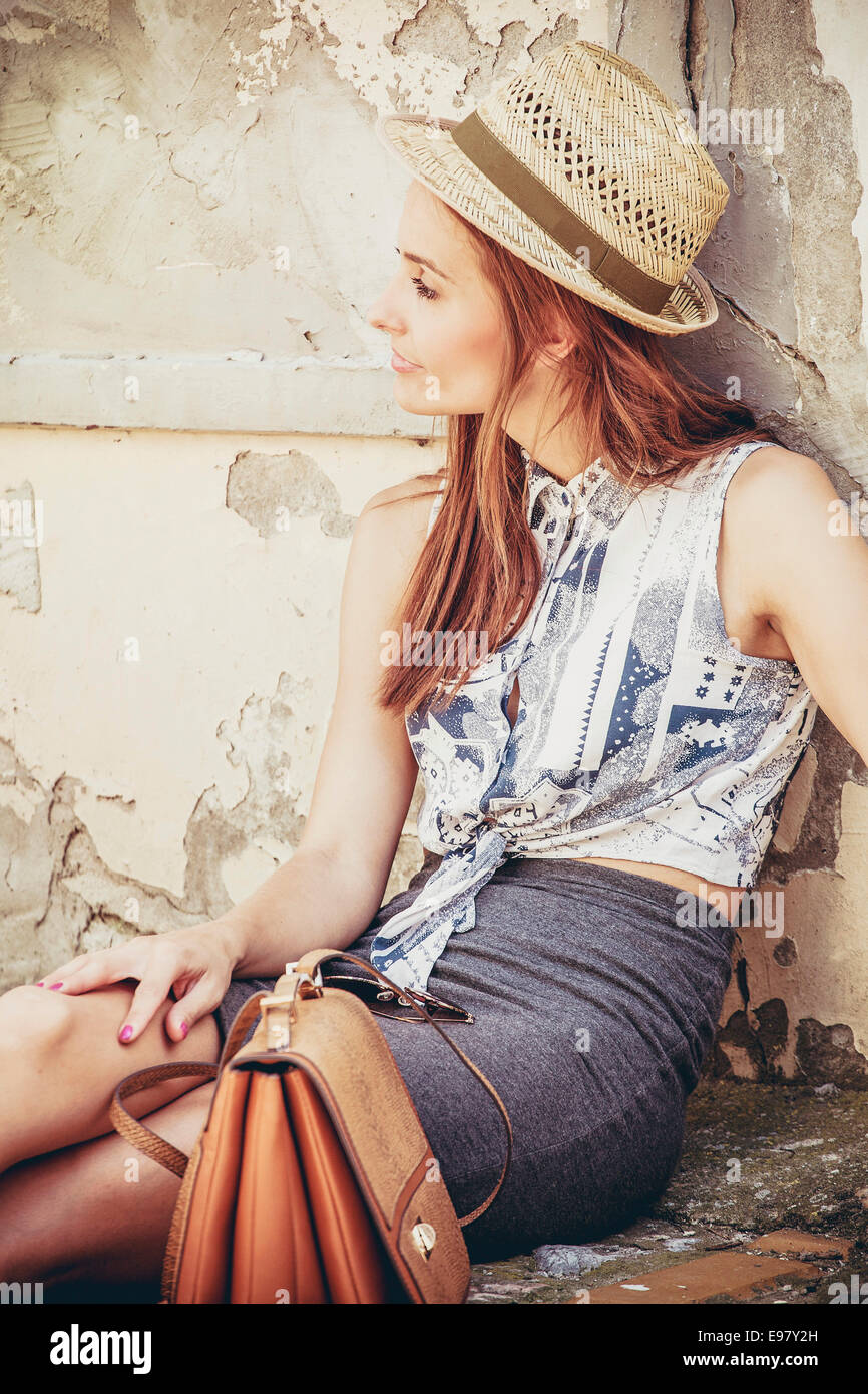 Young woman with sun hat waiting for departure outdoors - Stock Image