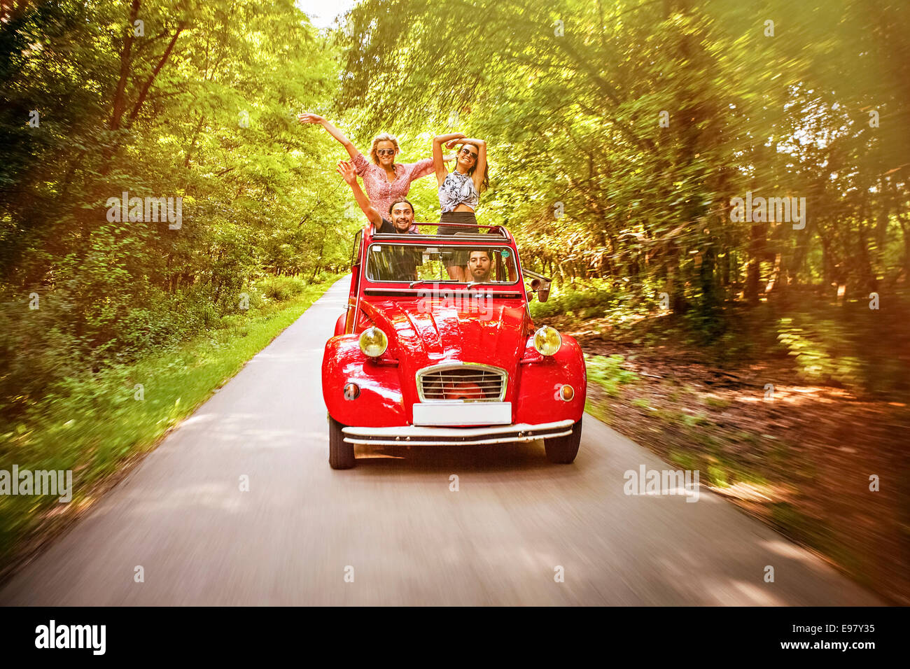 Young people in red vintage car having fun - Stock Image