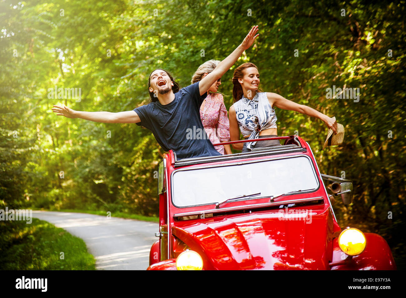 Young people in red vintage car fooling around - Stock Image