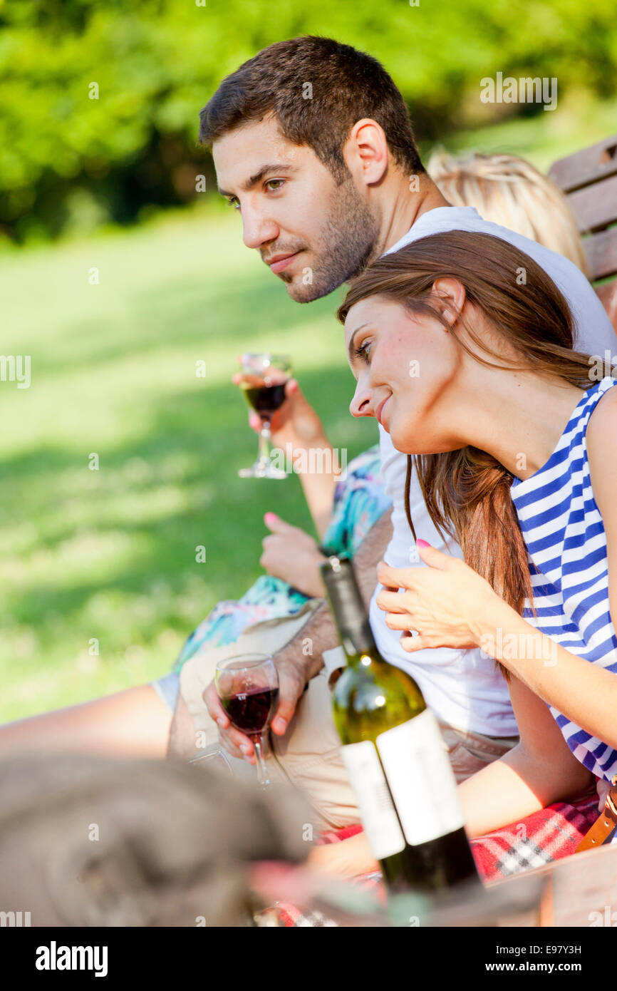Young people taking a break drinking red wine - Stock Image