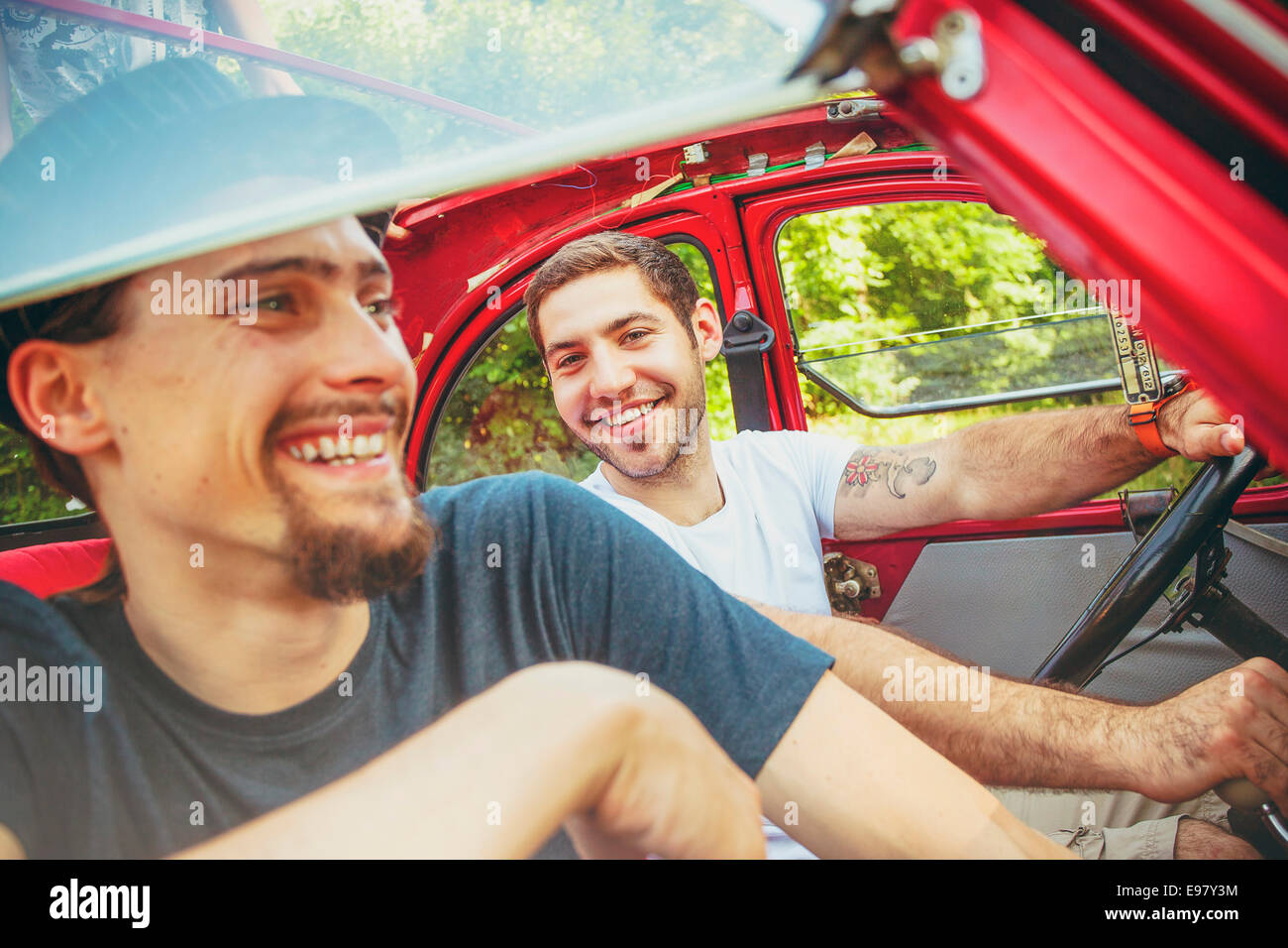 Portrait of two young men in red car smiling merrily - Stock Image