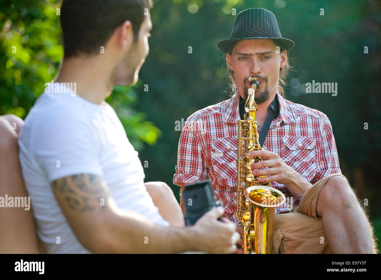 Young man playing saxophone, friend is listening - Stock Image