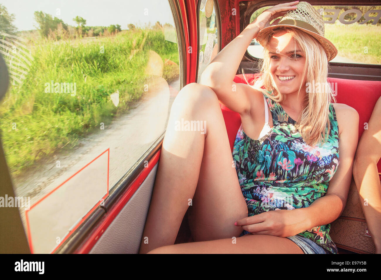 Woman on back seat of vintage car smiling happily - Stock Image