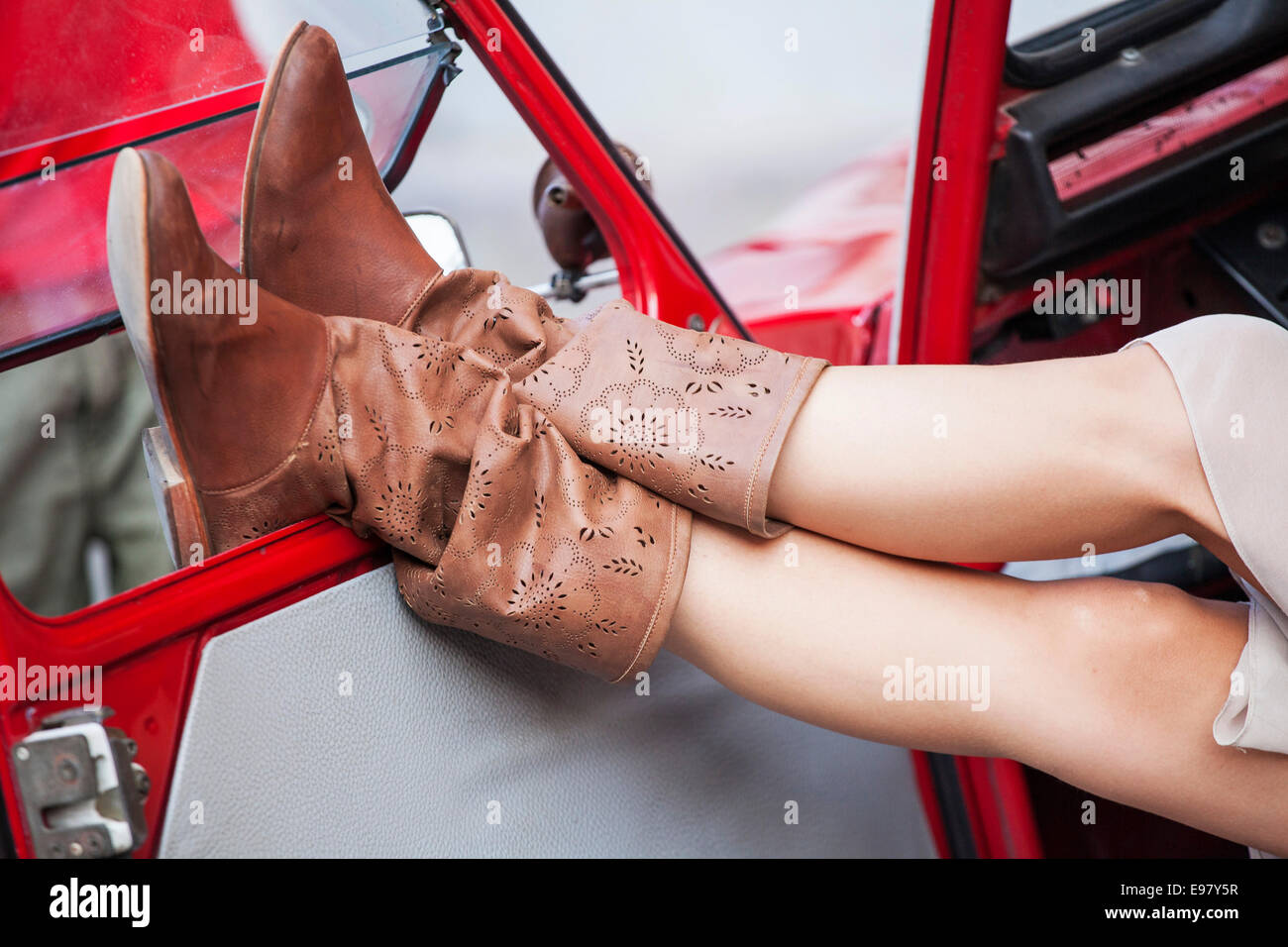 Young woman in leather boots relaxing in car - Stock Image