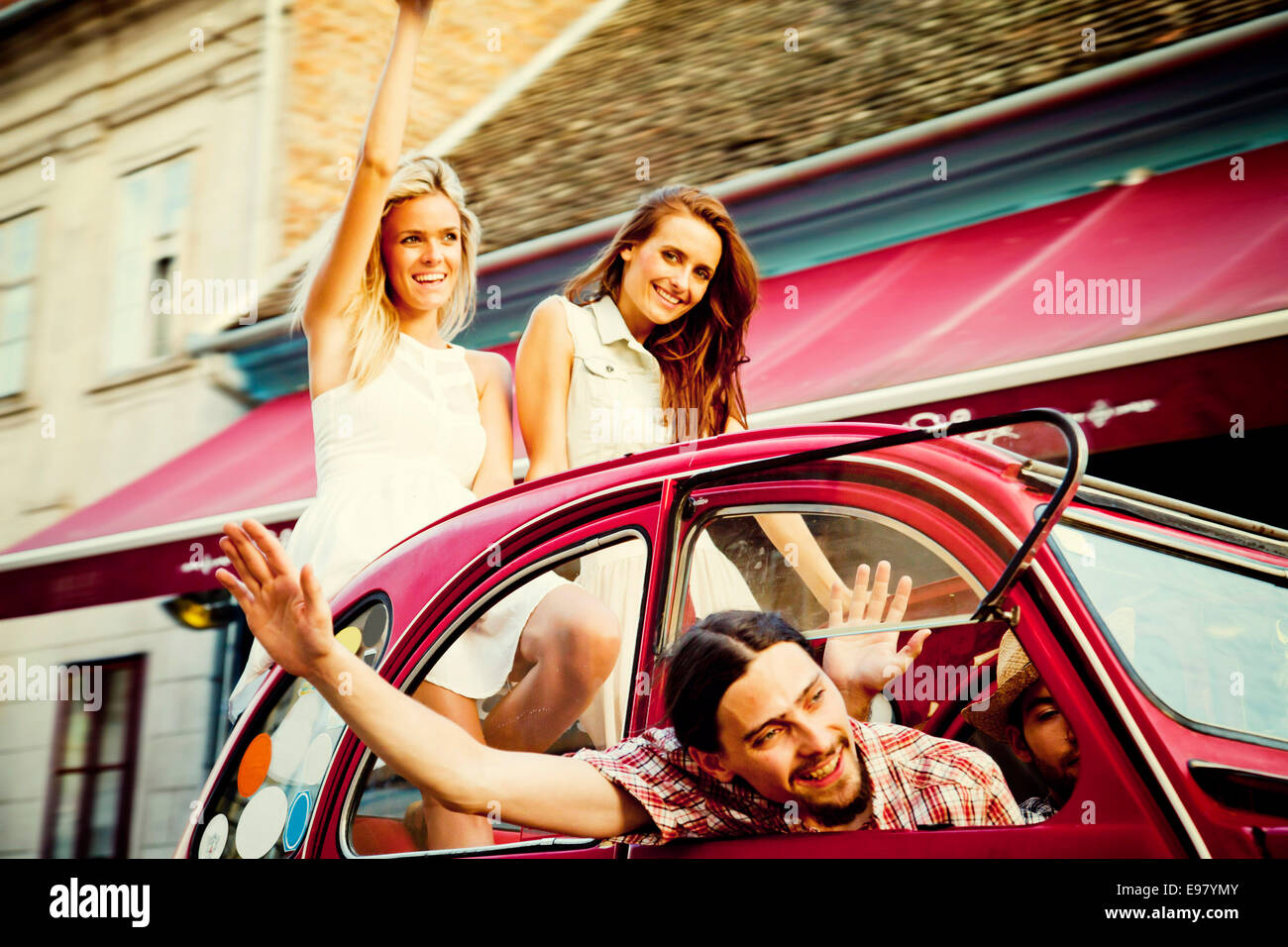 Young people driving in vintage car waving happily - Stock Image