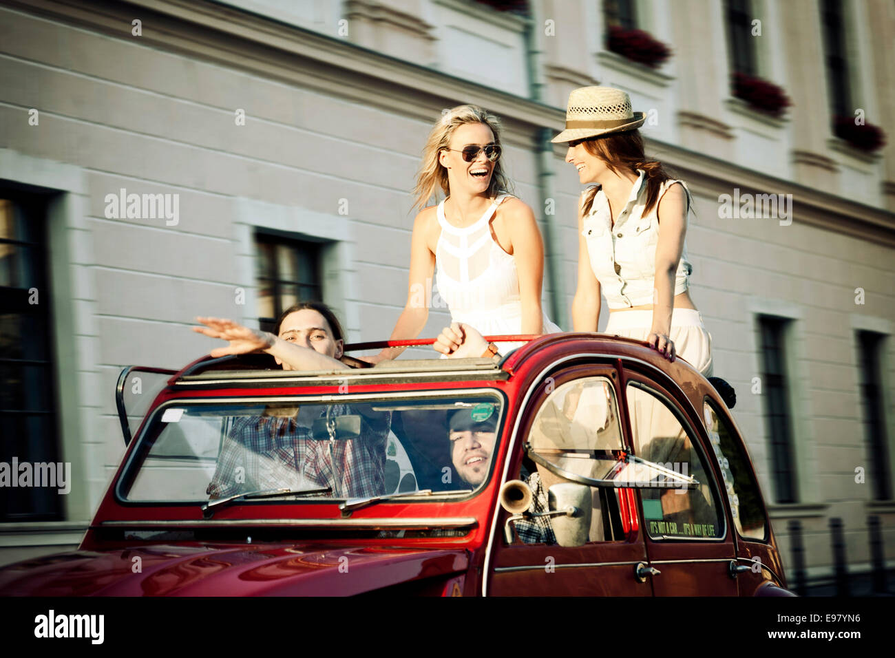 Young people in vintage car driving through city - Stock Image