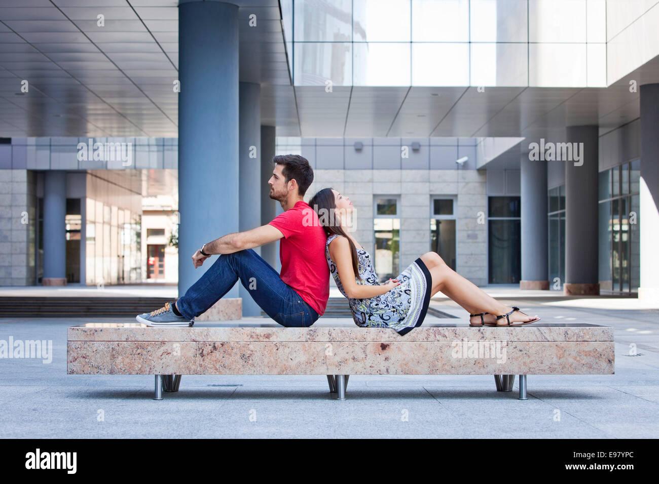 Female student leaning against her boyfriends back - Stock Image