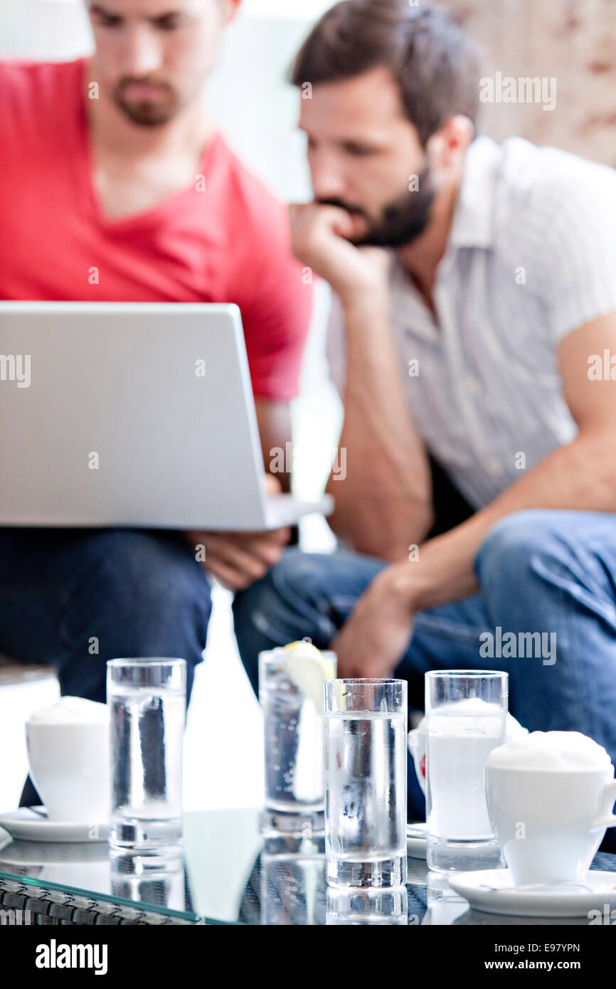 Two male university students in cafe working on laptop - Stock Image