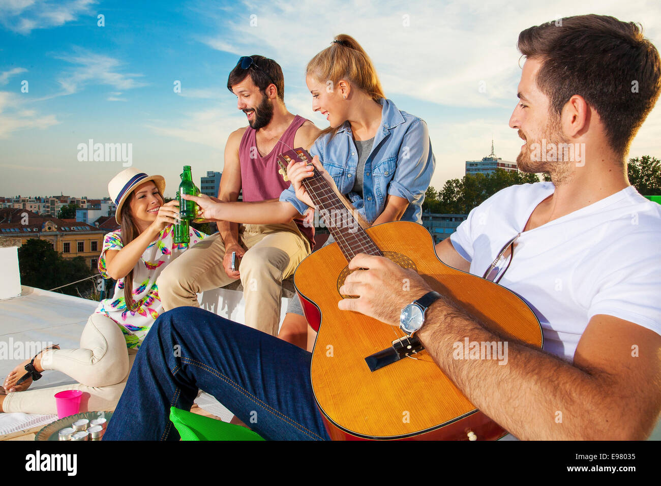 Young People Listening To Guitar Music At Rooftop Party