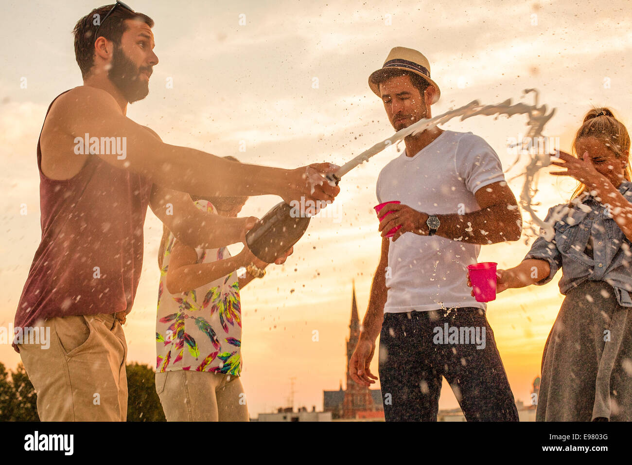 Young people at rooftop party fooling around - Stock Image
