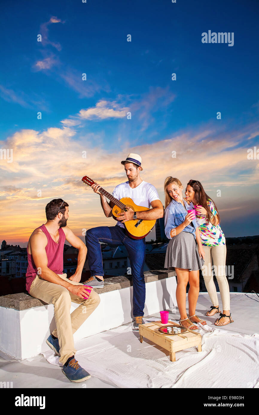 Young people listening to guitarist at rooftop party - Stock Image