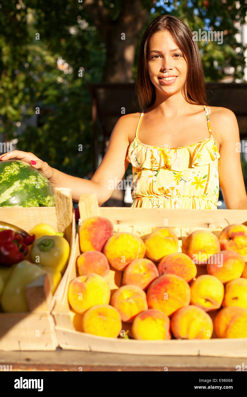 Woman selling fruit and vegetables at market stall - Stock Image