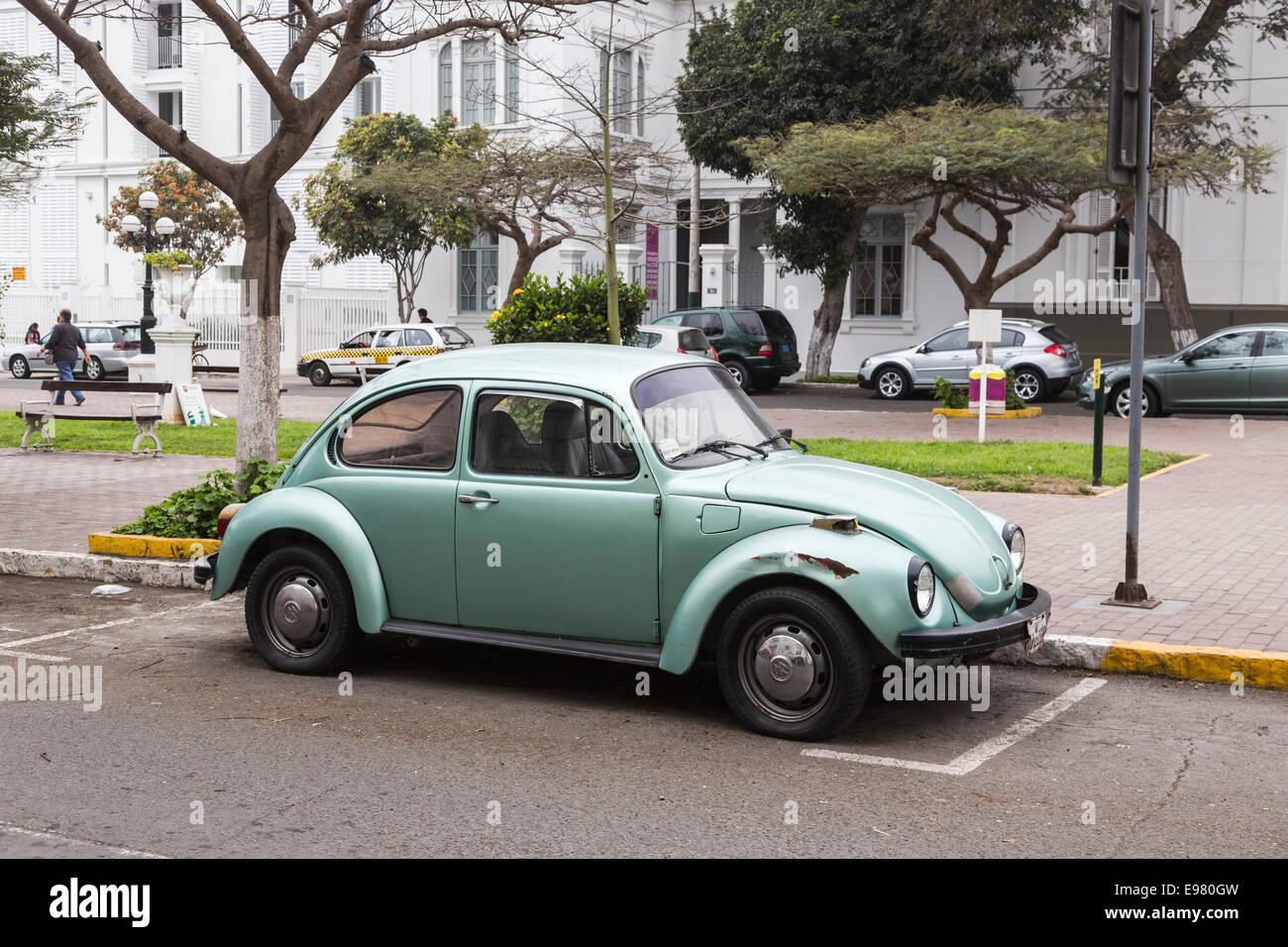 Green Volkswagen Beetle with damaged and rusty wheel arch in Barranco, Lima, Peru Stock Photo
