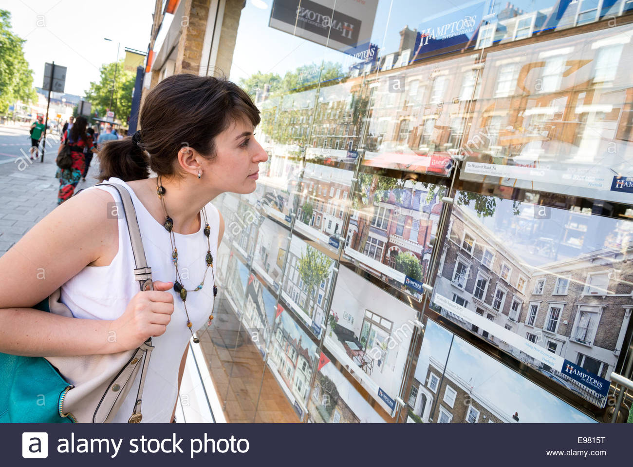 Young woman looking at houses for sale in estate agent window, Islington, London, England, UK - Stock Image