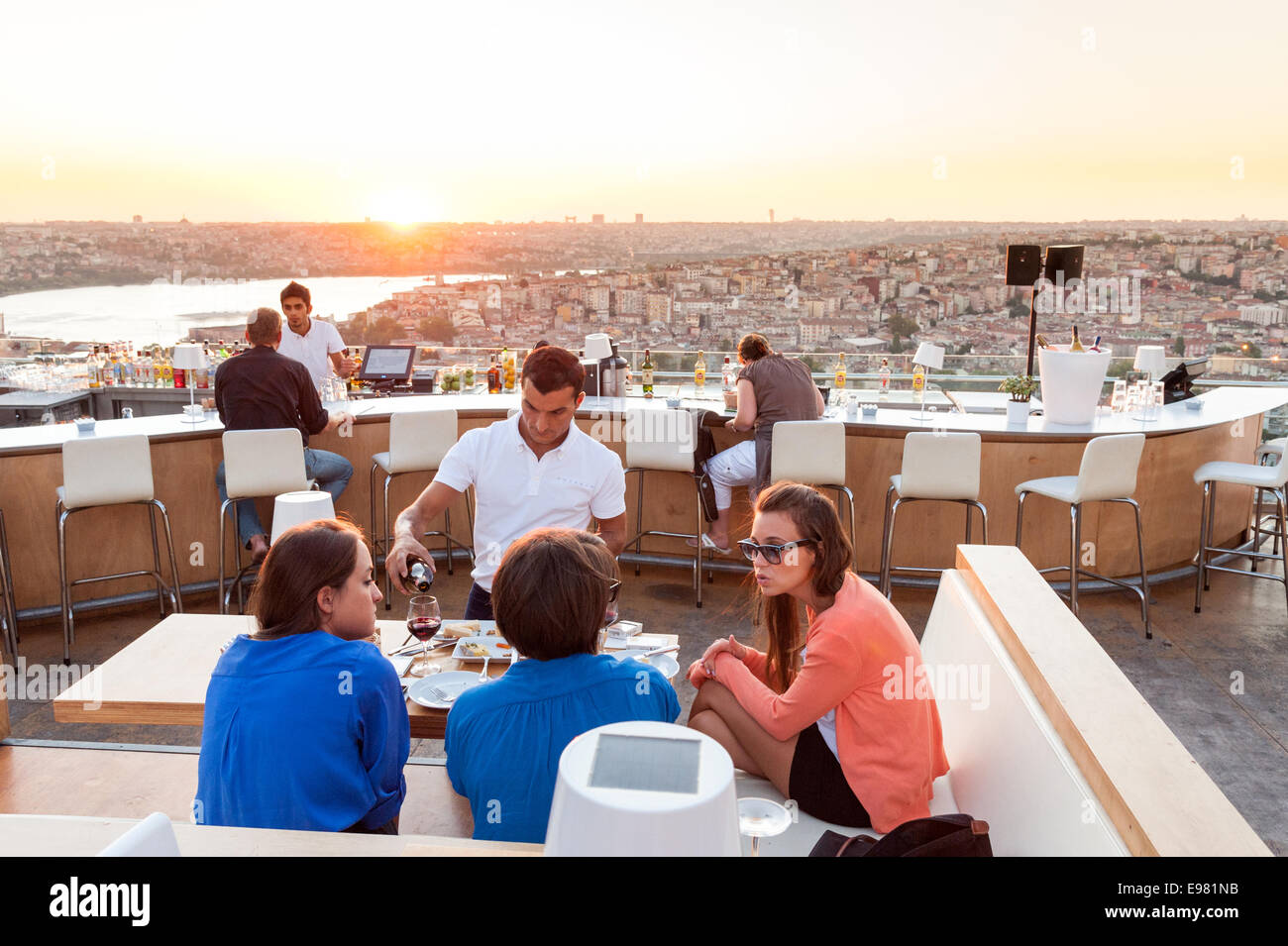 Fashionable young women at NuTeras rooftop bar and restaurant overlooking the Bosphorus, Beyoglu, Istanbul, Turkey - Stock Image