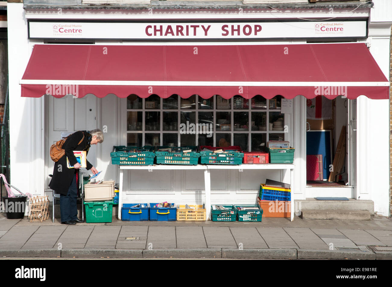 Woman browsing in a charity Shop, London, England, UK - Stock Image