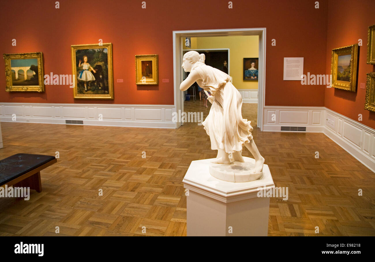 An exhibit of oil paintings, art, and sculpture inside a gallery at