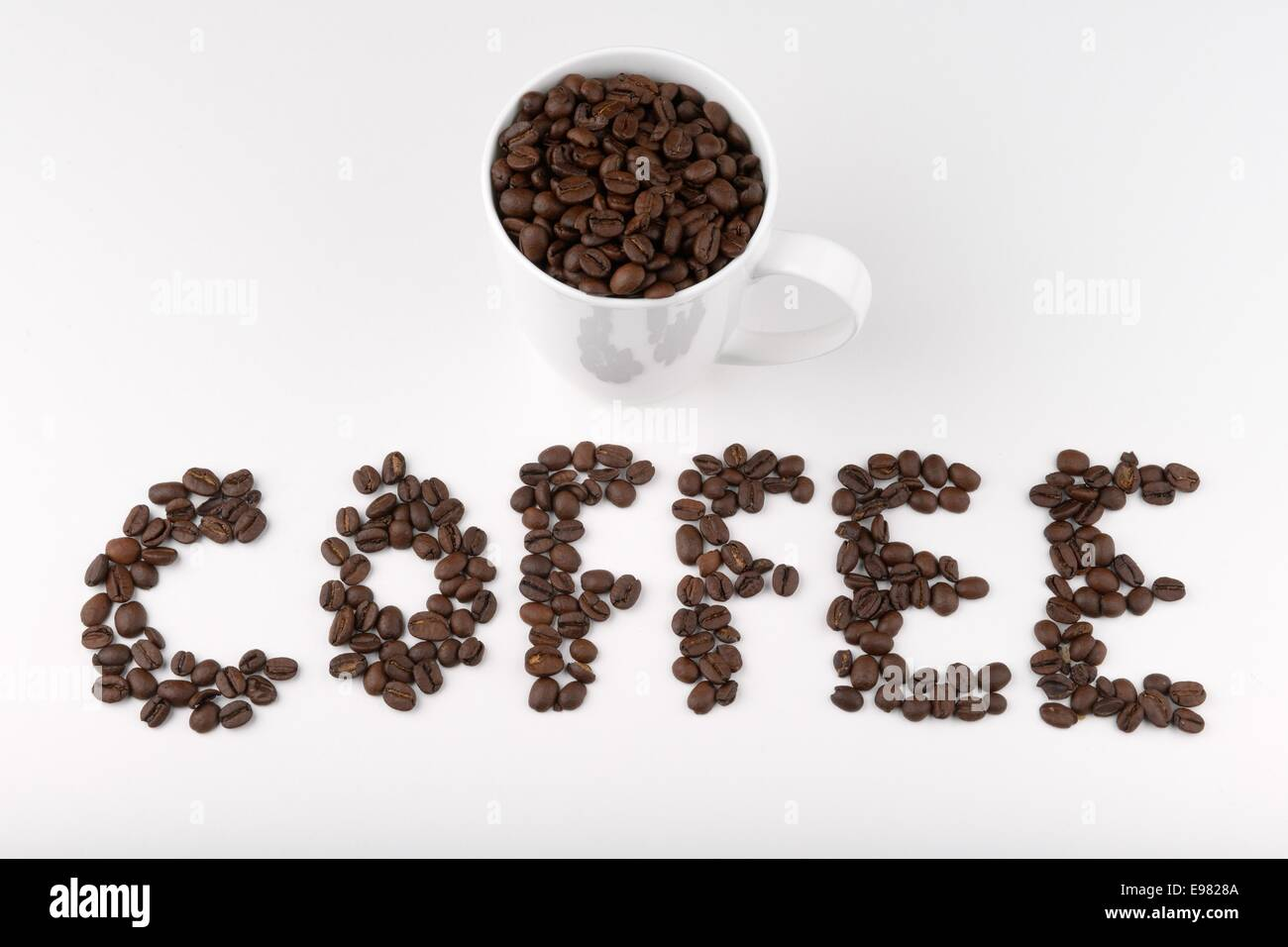 Coffee beans spelling out the word coffee and full cup - Stock Image