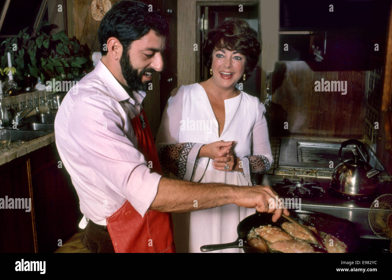 Liz Taylor in the kitchen of her Bel Air home cooking with Nick Grippo circa 1980s - Stock Image