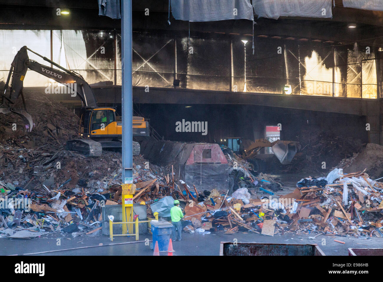 Garbage being sorted by backhoe, Downtown Los Angeles, California, USA - Stock Image
