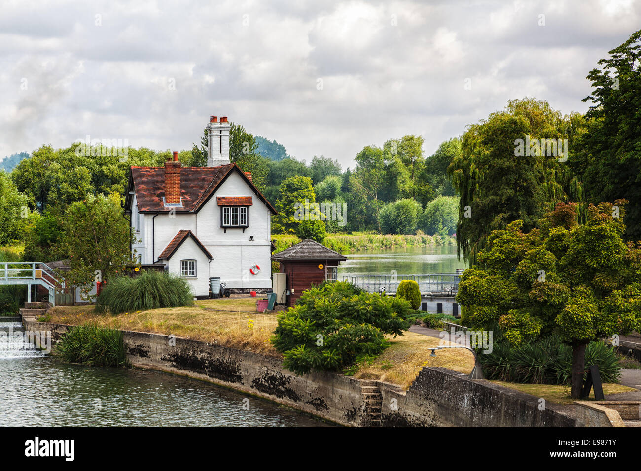 White house near the Thames River Canal, English countryside cottage beside the river canal. - Stock Image