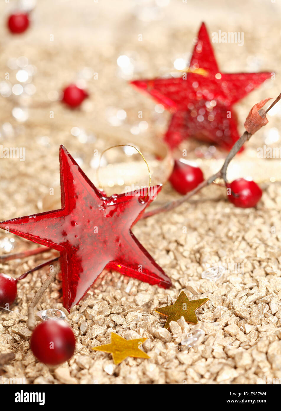 Red vitreous Christmas stars and two golden on a festive christmas background - Stock Image