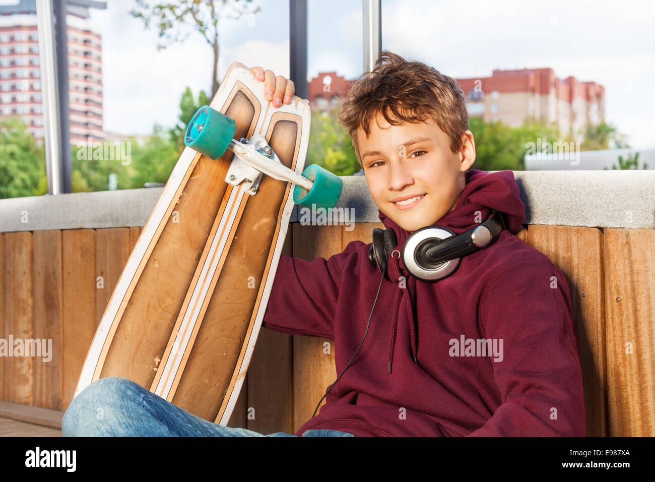 Positive cute boy holds skateboard while sitting - Stock Image