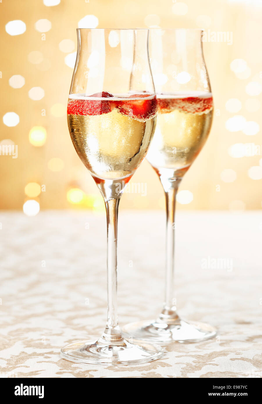 Festive champagne flutes filled with sparkling wine and floating strawberries with a backdrop bokeh of romantic - Stock Image