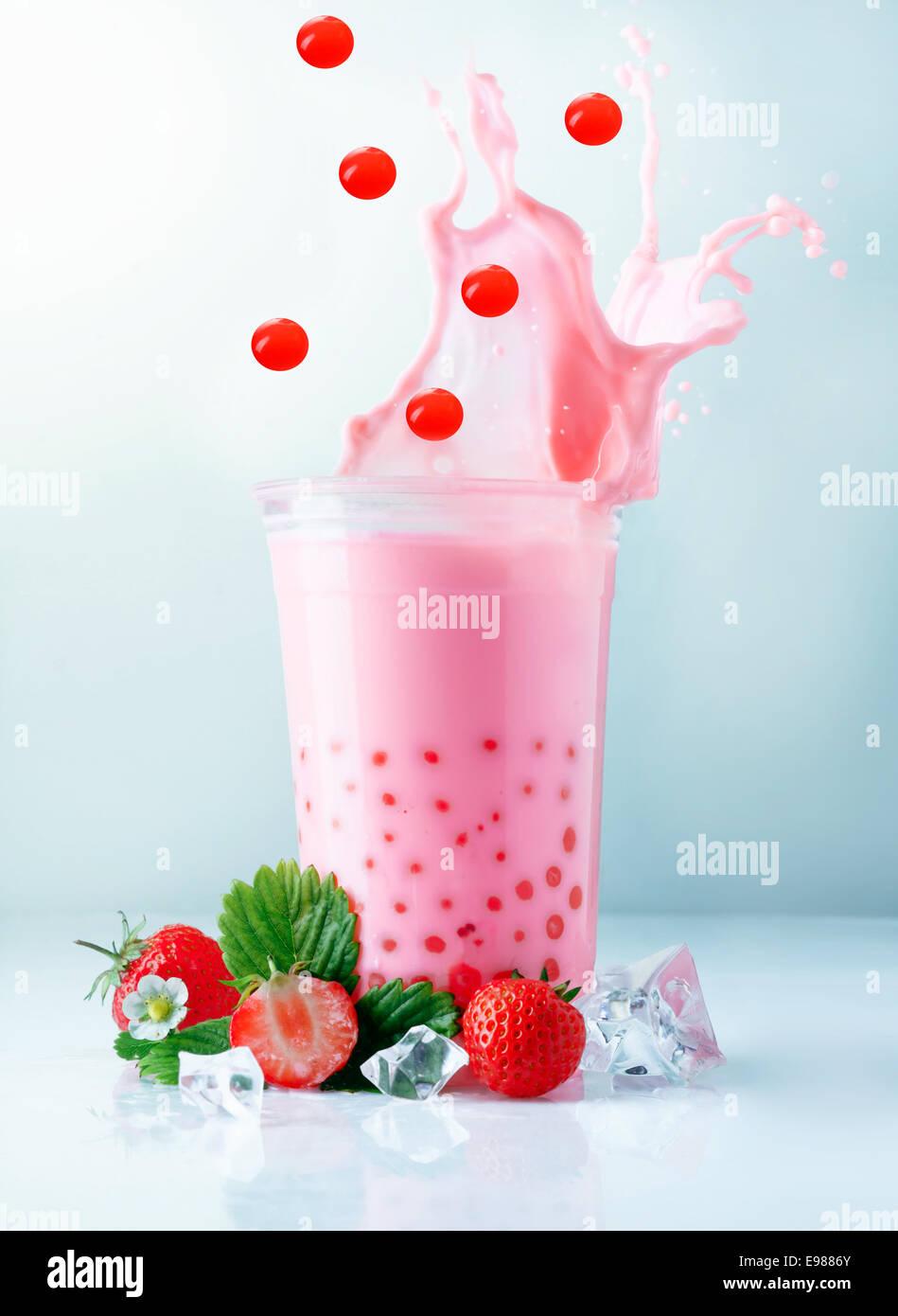 Fruity pink strawberry boba tea splashing from a glass ...