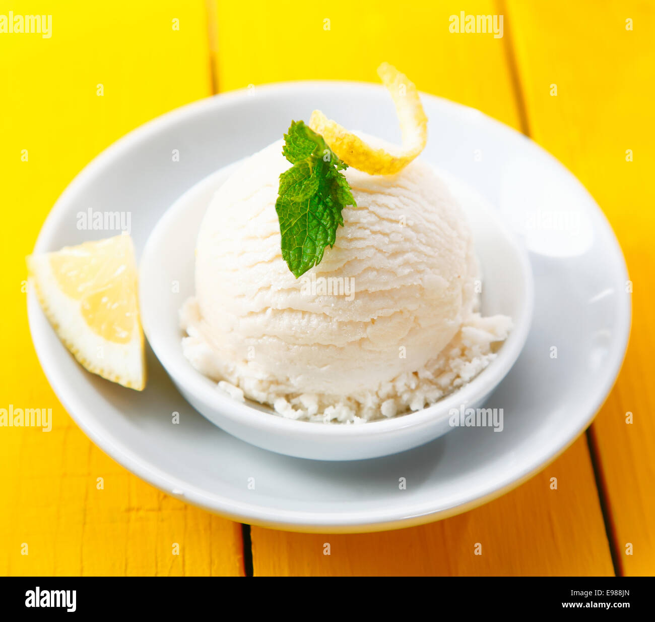 High angle view of a serving of refreshing tangy lemon sorbet served with zest and a slice of lemon - Stock Image