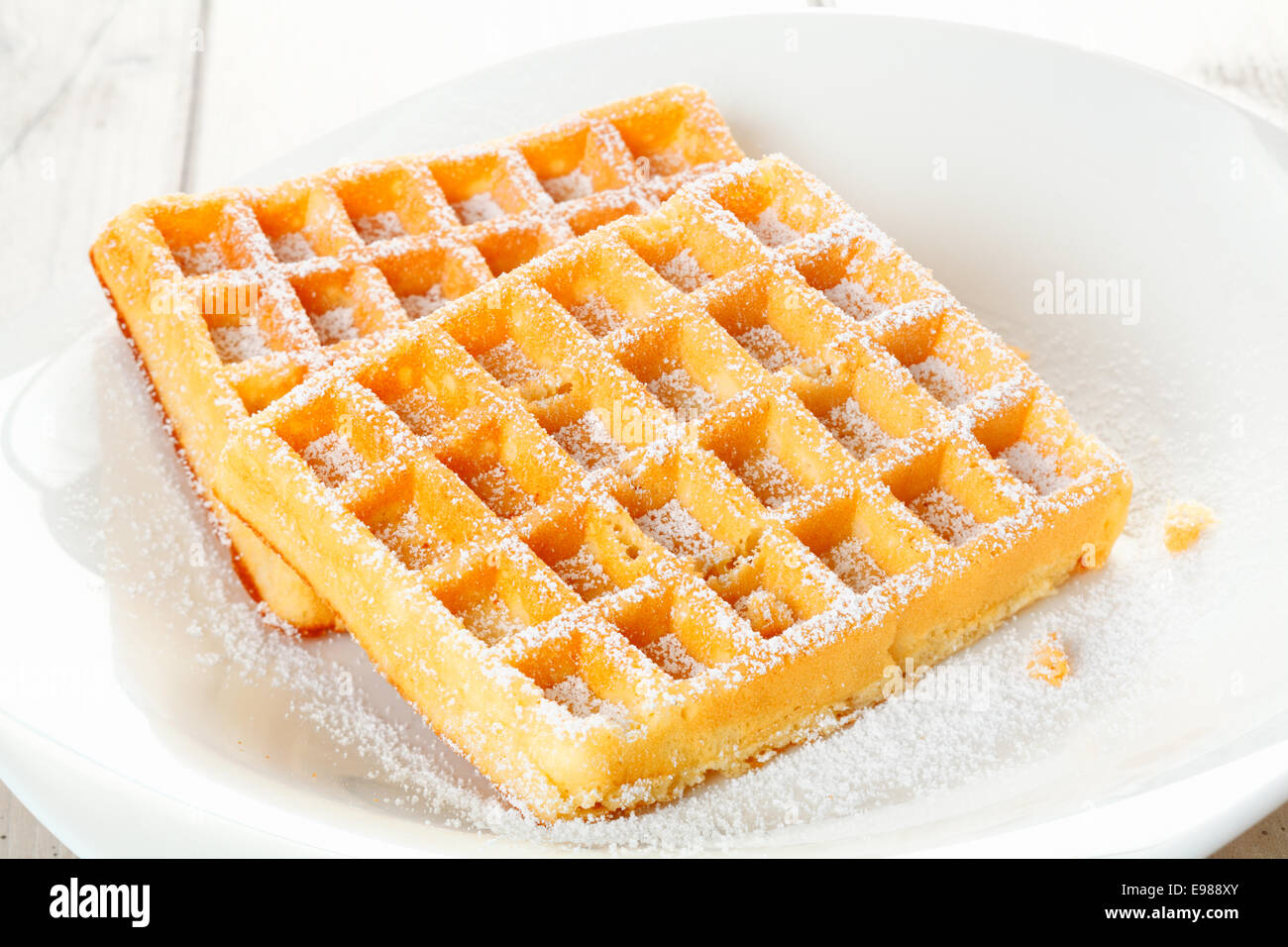 A pair of delicious fresh waffles, dusted with sugar an placed in a shallow white china bowl - Stock Image