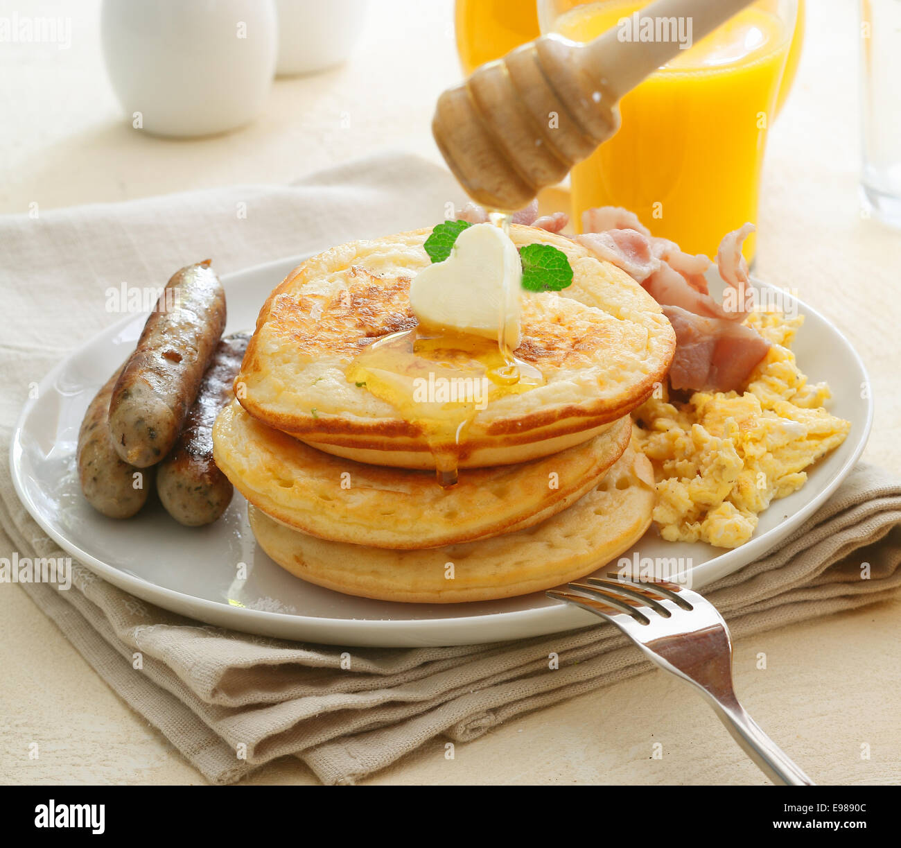 Large hearty cooked breakfast with sausages, eggs, bacon and a stack of golden pancakes topped with a drizzling - Stock Image