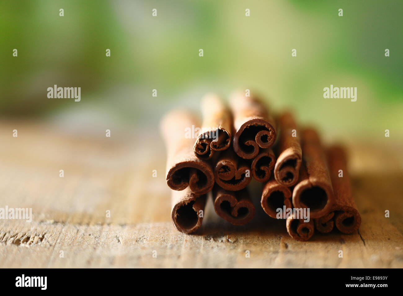 Closeup of a bunch of dried spicy cinammon sticks on a wooden surface with copyspace - Stock Image