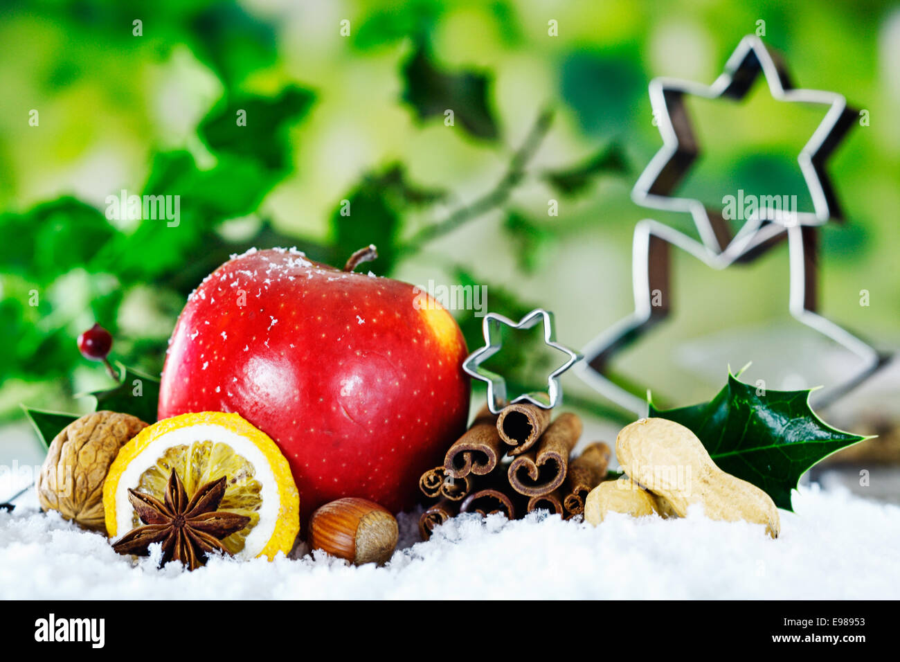 Christmas still life background with a red apple, nuts, and spices against green foliage with holly and stars Stock Photo