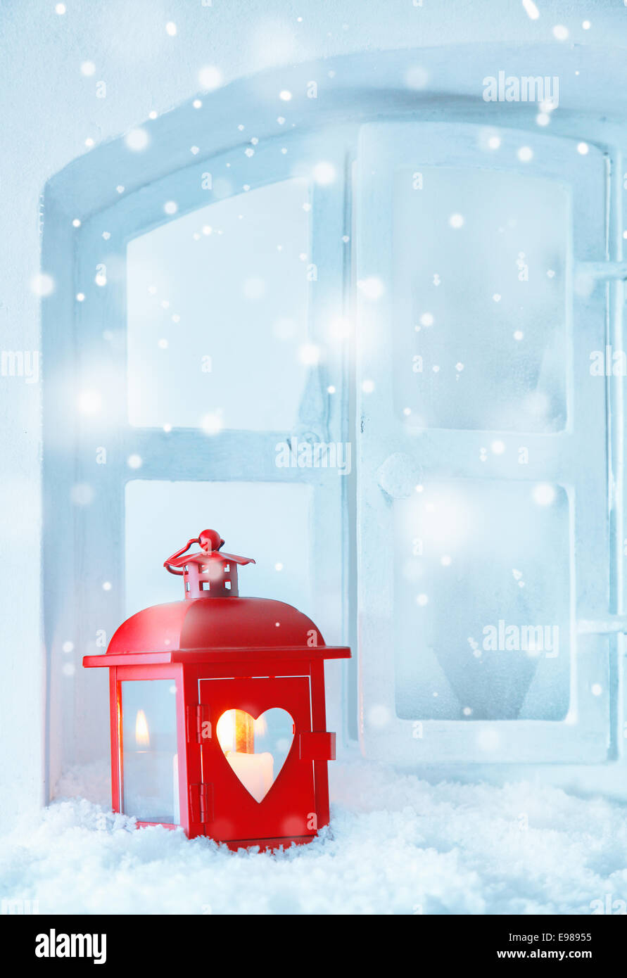 Red Christmas lantern guiding light with a glowing burning candle on a windowsill in falling snow with copyspace - Stock Image