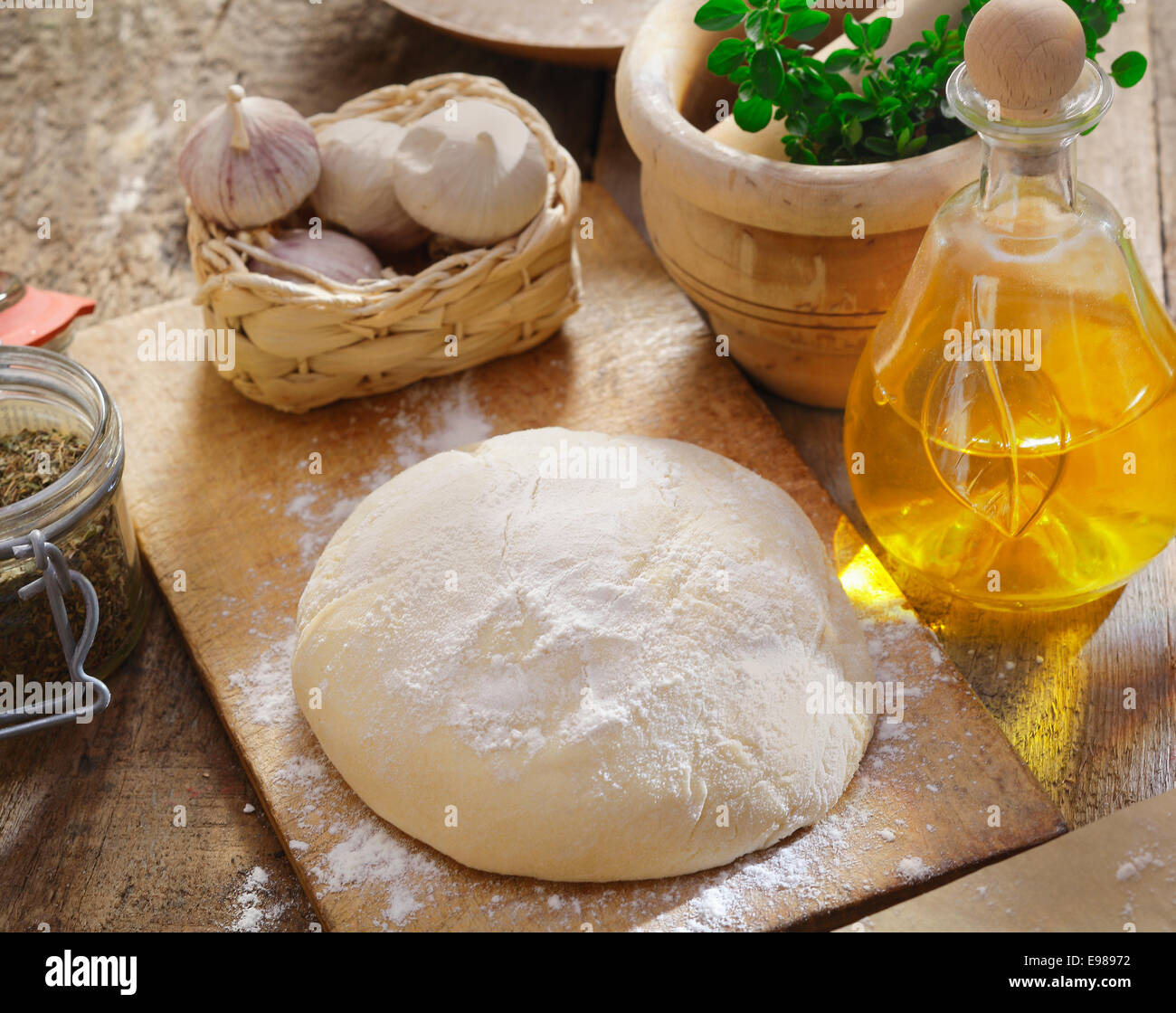 Pizza dough being left to rise surrounded by fresh herbs, garlic and ingredients in the kitchen Stock Photo