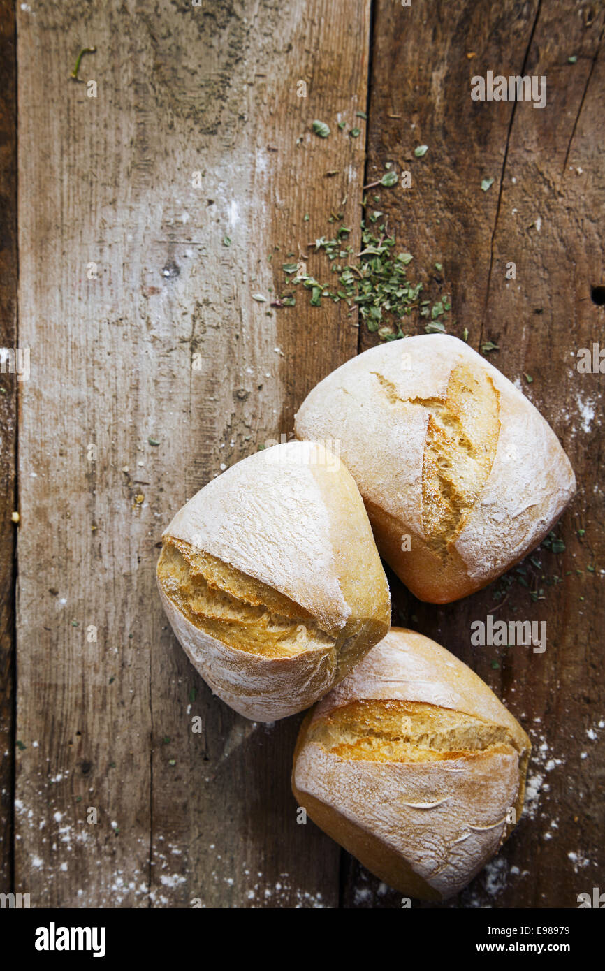 Fresh crusty bread rolls lightly dusted with flour on an old wooden surface with copyspace - Stock Image