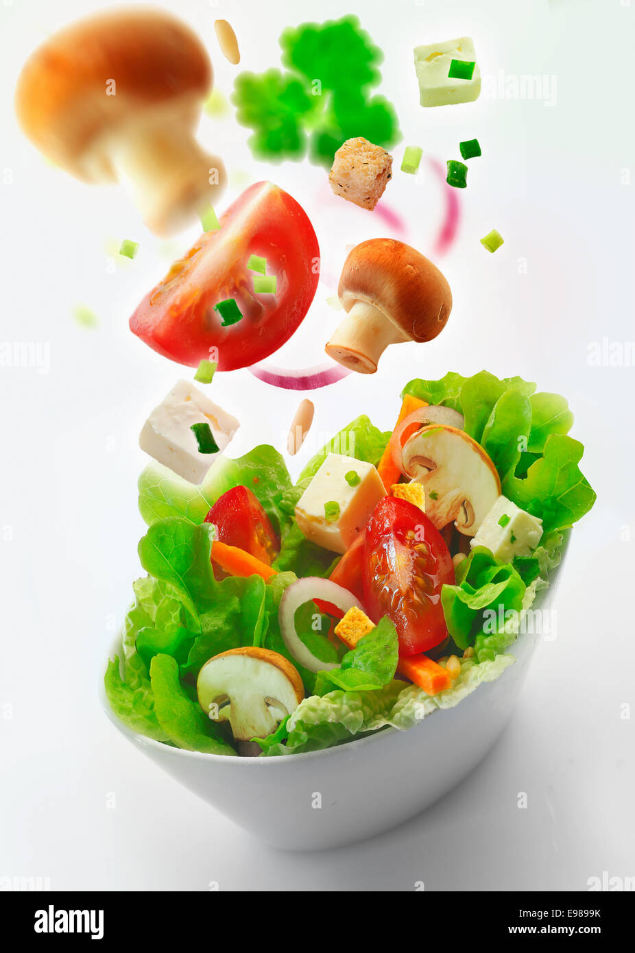 Individual side bowl of healthy fresh mixed green salad of lettuce, carrot, onion, mushrooms, tomato and feta with - Stock Image