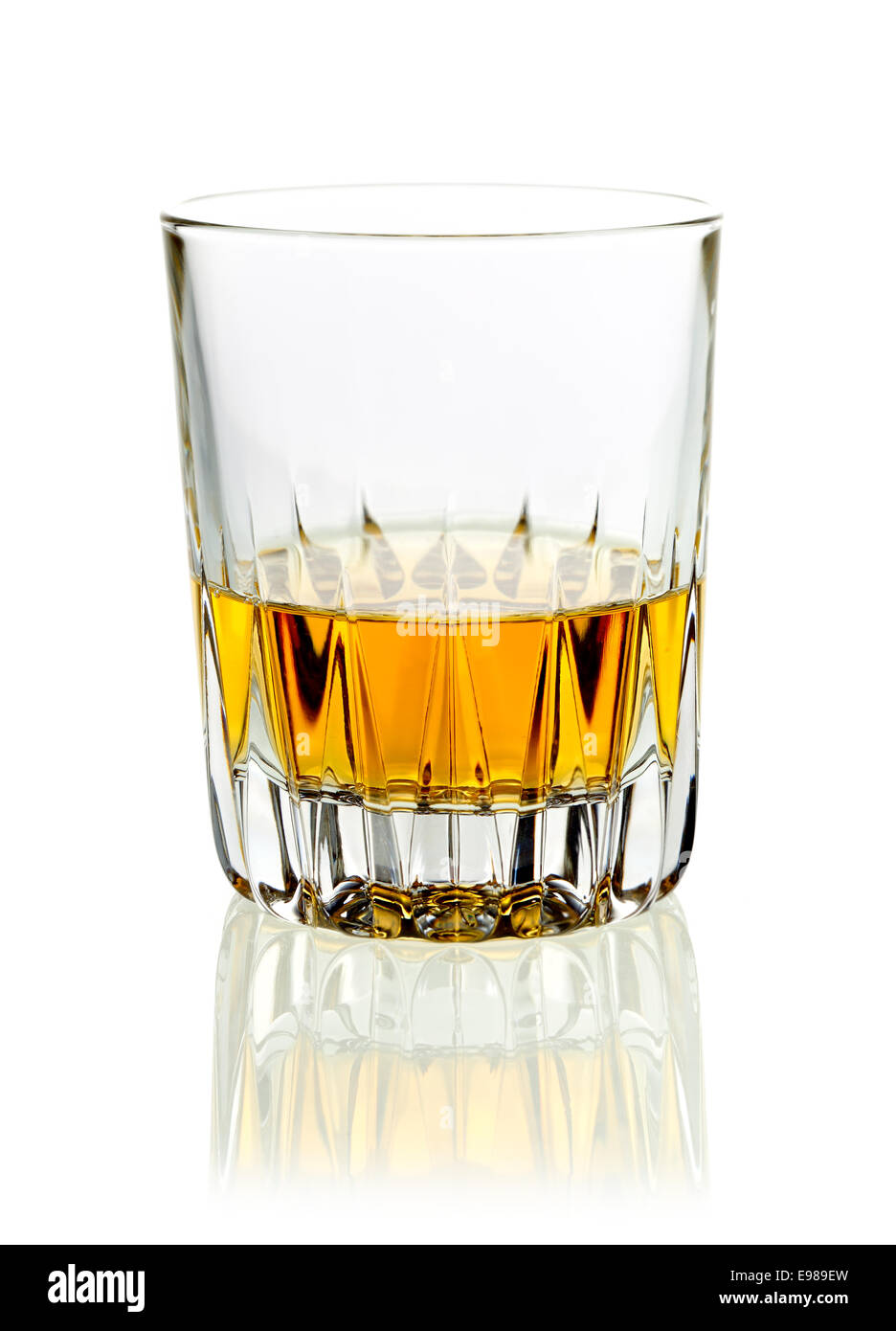 Tumbler of golden whisky or brandy served neat on a white studio background with reflection - Stock Image