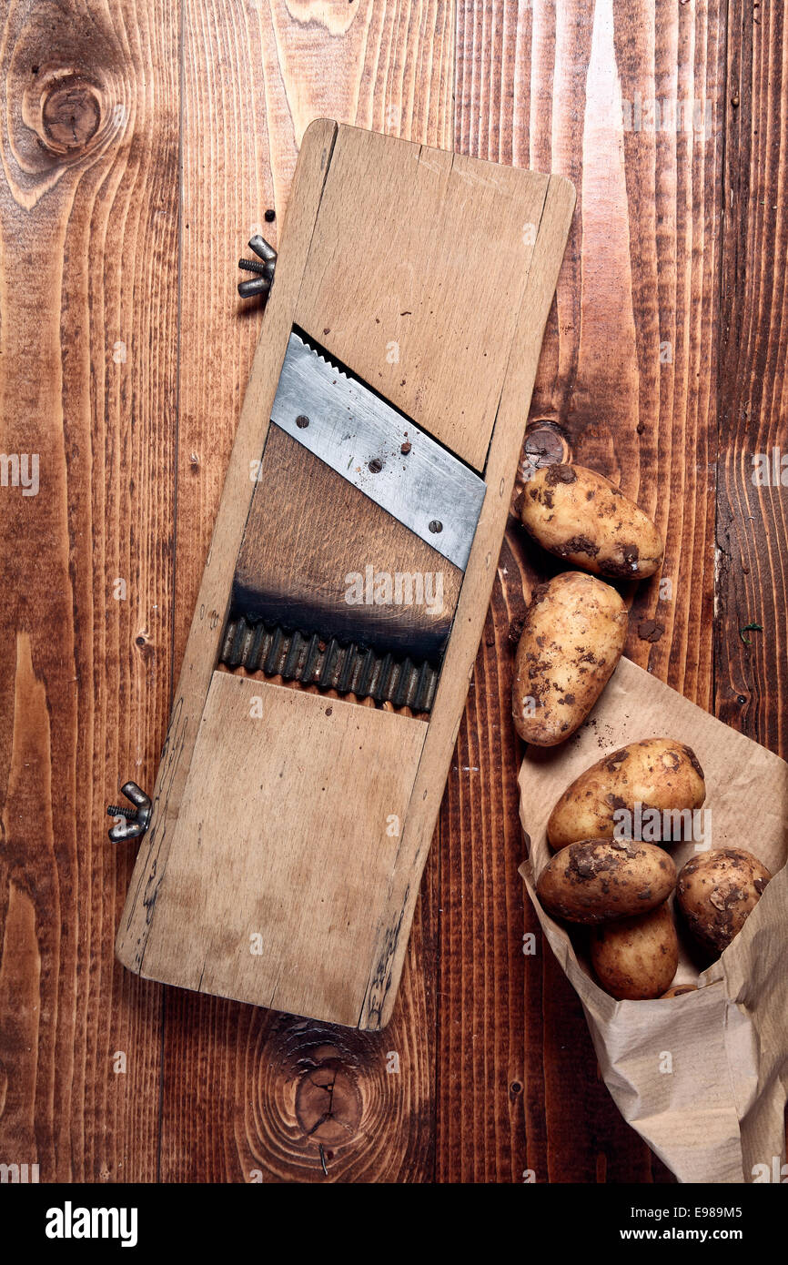 Fresh earthy unwashed potatoes and a vintage cutter with an adjustable blade on a wooden tabletop - Stock Image