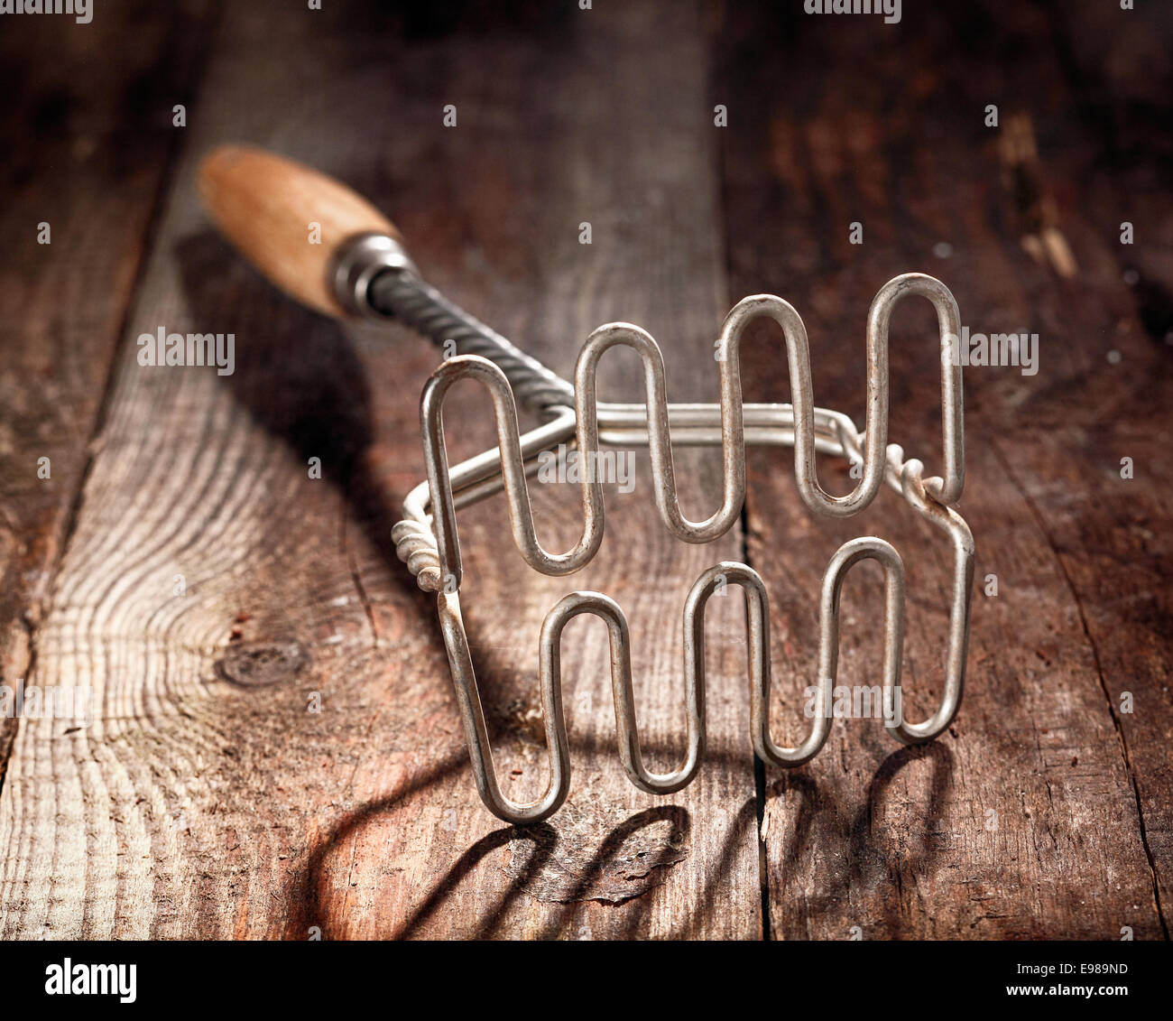 Old wood and metal potato masher on a textured wooden surface with shallow dof and focus to the steel wire grid - Stock Image