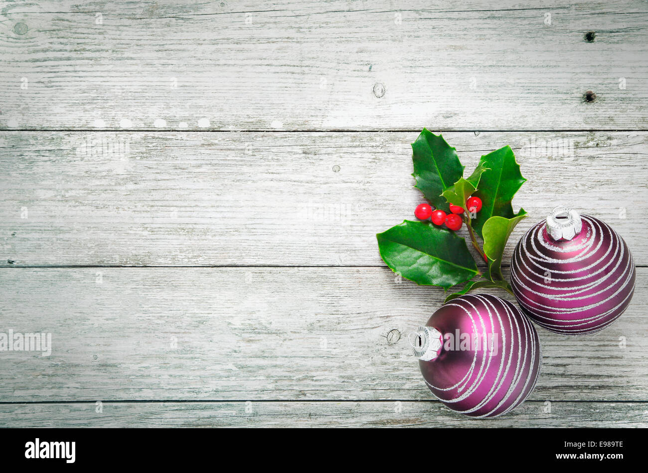 Christmas holly and pretty purple baubles with a spiral pattern on rustic wooden white painted boards with woodgrain Stock Photo