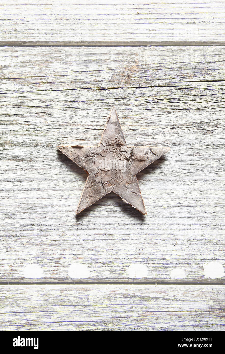 Old grungy Christmas star centred vertically on weathered planks with woodgrain and copyspace - Stock Image