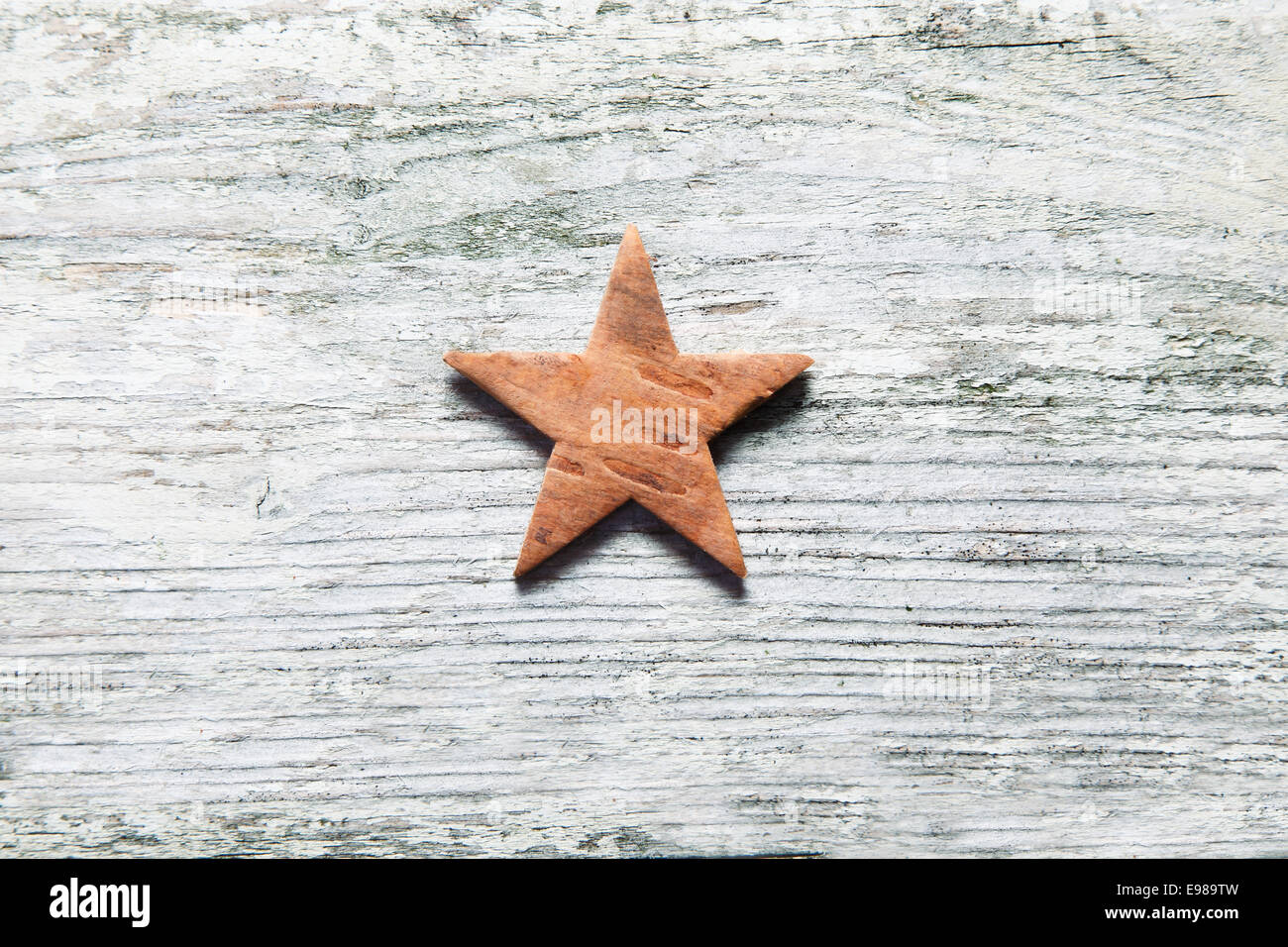 Rustic Christmas star centred on grungy old white weathered wooden boards with grain texture and copyspace - Stock Image