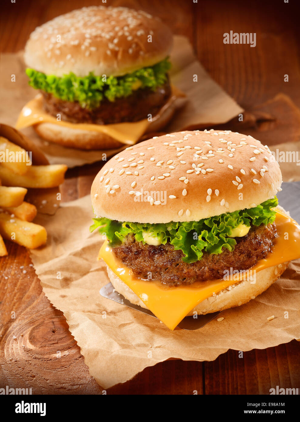 Two hamburgers and french fries on brown paper - Stock Image