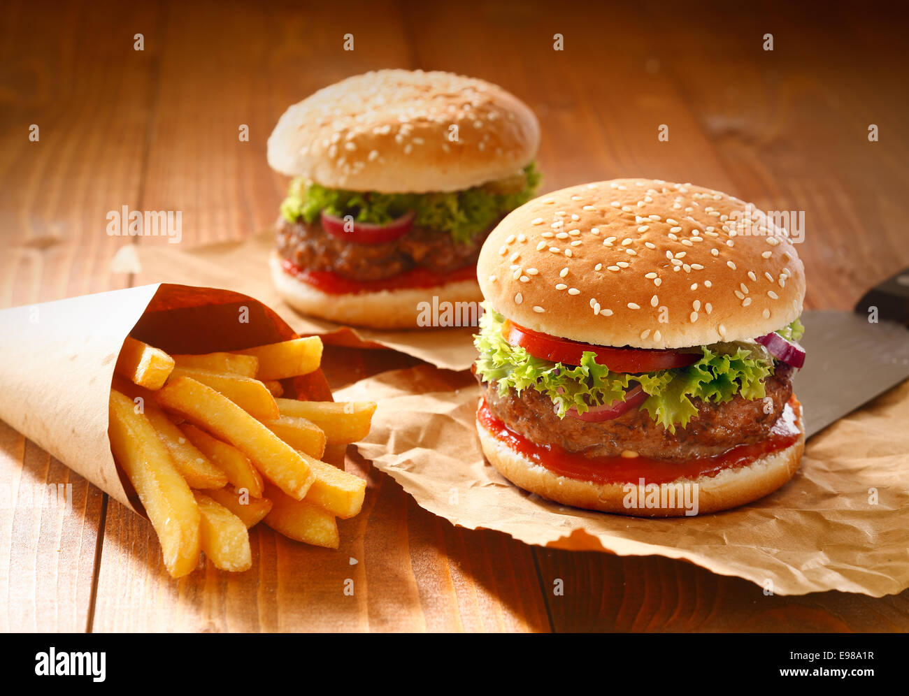 Two hamburgers and french fries with sesame bun on brown paper - Stock Image