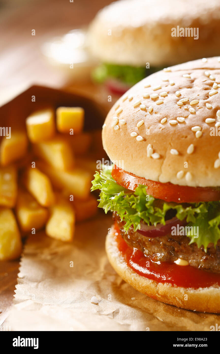 Two hamburgers and french fries with sesame bun on brown paper. selective focus - Stock Image